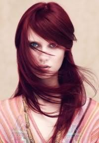 Стрижка каскад з косою чубчиком на довге волосся темно-червоного кольору стильно виглядає в тандемі з денним макіяжем для блакитних очей і світлої шкіри