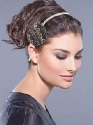 Каштановий колір волосся чудово виглядає в грецькій зачісці на середню довжину у вигляді високого хвоста з локонами, прикрашеної тонким сірим обідком і поєднуються з макіяжем в сірих і коричневих тонах