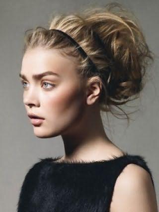 Стильна грецька зачіска на довге світле волосся у вигляді хаотично покладених локонів, зафіксованих тонким чорним обідком, в поєднанні з природним макіяжем очей і помадою світло-коричневого тону