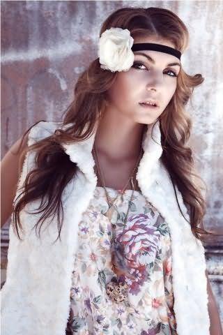 Грецька зачіска у вигляді розпущених локонів, зафіксованих гумкою чорного кольору з білою квіткою, добре виглядає на довгому волоссі світло-каштанового відтінку і поєднується з макіяжем в коричневій гамі