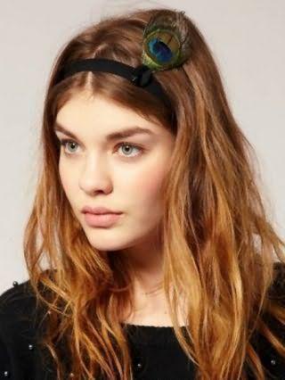 Довге волосся карамельного відтінку відмінно виглядають в грецькій зачісці на розпущене пасма, прикрашеної гумкою з павичевим пером, і доповнюються природним макіяжем для зелених очей і помадою натурального тону
