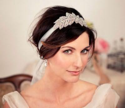Природний макіяж сіро-зелених очей гармонує зі світлим блиском для губ і доповнює весільну зачіску з стрічкою, декорованого стразами, на волоссі каштанового відтінку