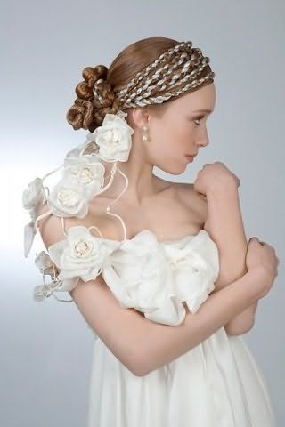Ніжний весільний образ у вигляді гармонійного поєднання макіяжу в природних тонах і зачіски зі стрічками, вплетеними в коси навколо голови, сріблястого відтінку на довгому волоссі світло-русявого кольору