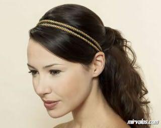 Темно-русявий колір волосся добре виглядає на зачісці з тонким подвійним обідком, у вигляді хвоста на потилиці, покладеного в локони, і гармонує з денним макіяжем в світло-коричневих тонах