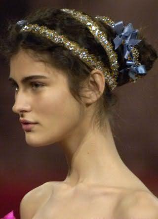 Темно-русявий колір кучерявого волосся добре виглядає на грецькій зачісці, зафіксованої довгою стрічкою зі стразами і невеликими бантиками, і гармонує з природним макіяжем для карих очей і теплого кольоротипу зовнішності