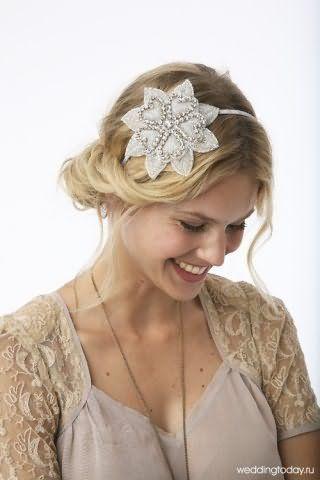 Хвилясті довге волосся пшеничного відтінку, укладені в грецьку зачіску з тонким обідком, декорованим квіткою сріблястого відтінку, доповнять образ дівчини з природним макіяжем