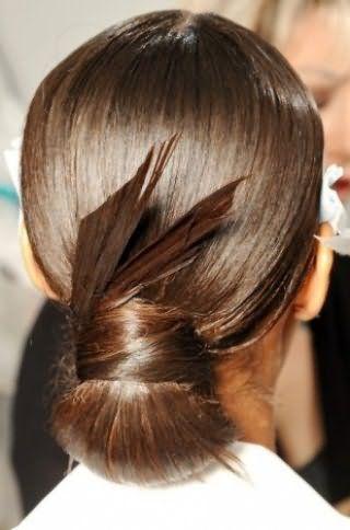Довге пряме волосся відмінно виглядають в оригінальному низькому пучку, перемотати широкої пасмом, кінці якого виступають елементом прикраси і надійно зафіксовані лаком