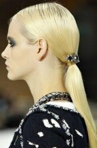 Модний варіант річної зачіски у вигляді хвоста, доповненого декоративною прикрасою, відмінно виглядає на довгих прямих волоссі відтінку блонд