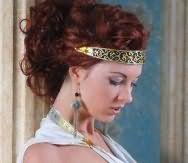 Кучеряві довгі локони відтінку червоне дерево доповнять вечірній образ дівчини з високою грецької зачіскою з широким металевим обідком бронзового відтінку і легким макіяжем