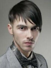 Асиметрична чоловіча стрижка з поголеними скронями та подовженою чубчиком на один бік гармонує з темно-русявим кольором волосся прямого типу і карими очима