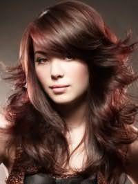 Варіант довготривалої укладання довгих або середніх волосся в хаотичному вигляді прекрасно виглядає з об`ємною косою чубчиком і колорованого пасмами