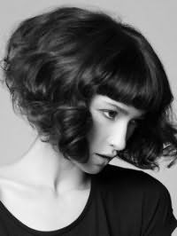 Хвилясте волосся чорного кольору на стрижці боб з прямою густий чубчиком доповнять природний макіяж очей і світла помада