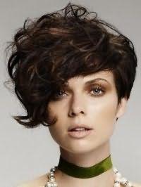 Асиметрична стрижка боб на кучеряве волосся каштанового кольору добре поєднується з макіяжем для сіро-зелених очей, виділених коричневими тінями і помадою бежевого кольору