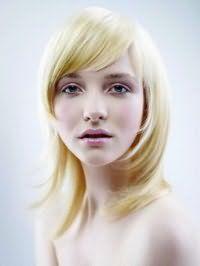 Правильна каскадна стрижка для довгого волосся і овальної форми обличчя, доповненої чубчиком на бік, дивовижно поєднується зі світлим волоссям з легким жовтим відтінком